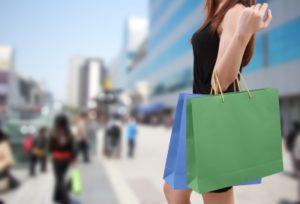 ショッピングバックを持つ黒服の女性